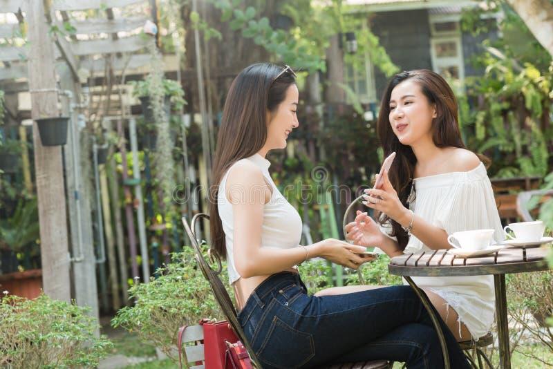 Two Beautiful freelance woman use social media on smartphone in. Two Beautiful freelance women use social media on smartphone in coffee shop, modern generation royalty free stock photos
