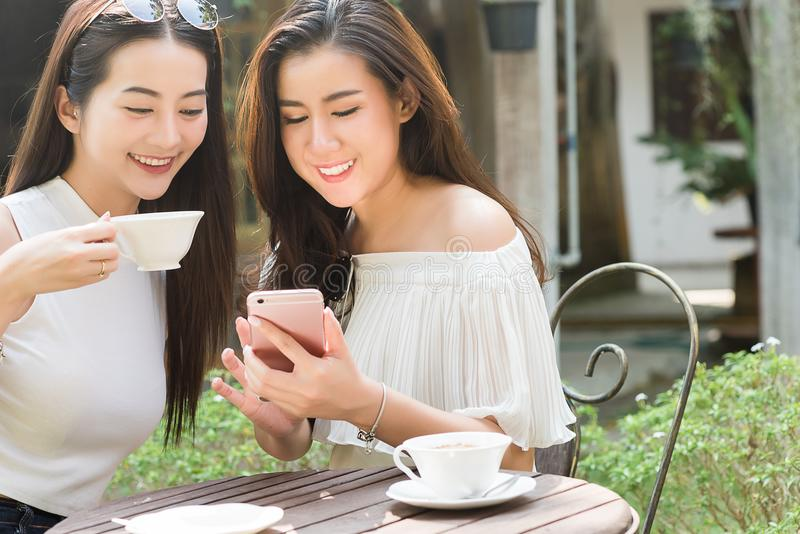 Two Beautiful freelance woman use social media on smartphone in. Two Beautiful freelance women use social media on smartphone in coffee shop, modern generation stock images