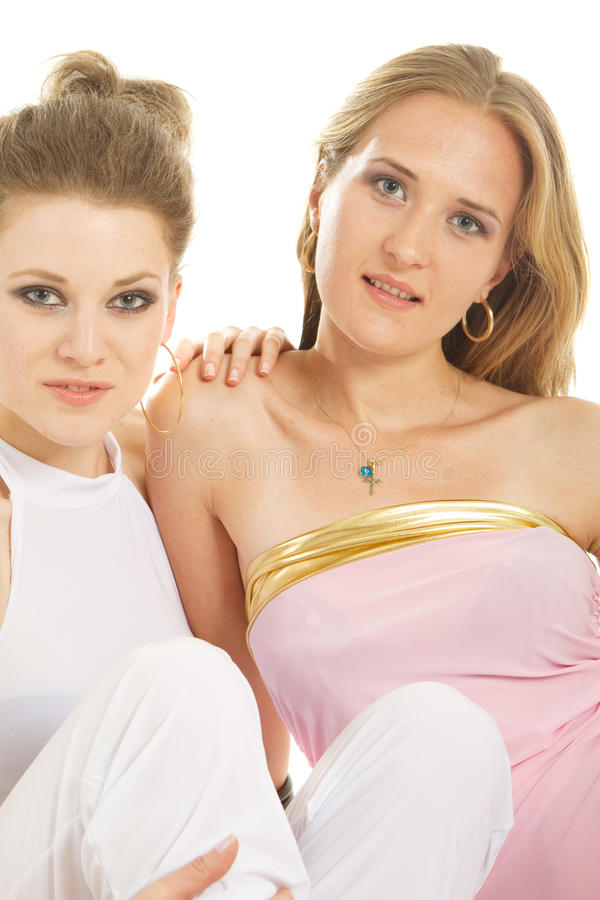 Two beautiful friends. Two young female models relaxing on the floor. Isolated studio shot stock photo