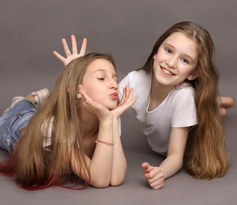Two beautiful, funny friends, 9 years old, on a photo shoot in the studio stock photo