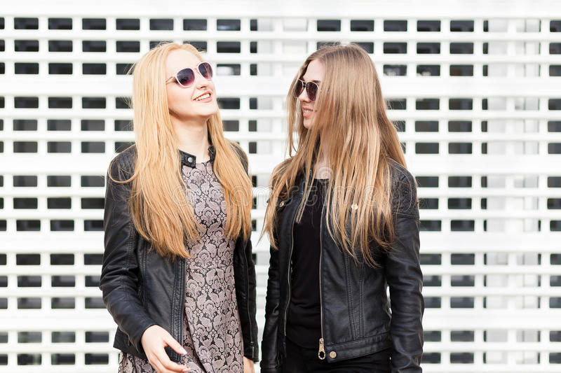 Two beautiful girl friends having fun outside in the city. Friendship and urban lifestyle stock photography