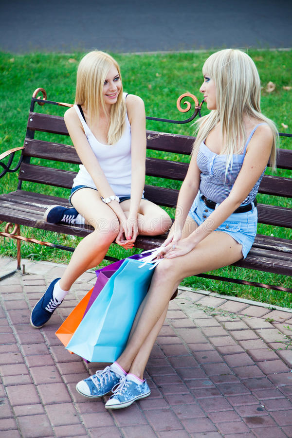 Two beautiful girl friends with shopping bags stock images