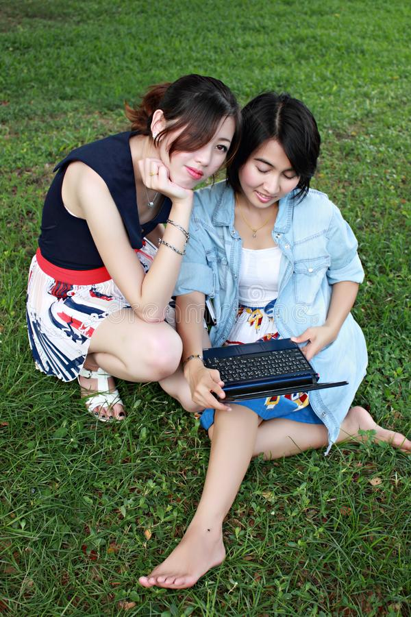 Download Two Beautiful Girl On A Laptop Computer Outdoors. Stock Photo - Image of jeans, beautiful: 16511932
