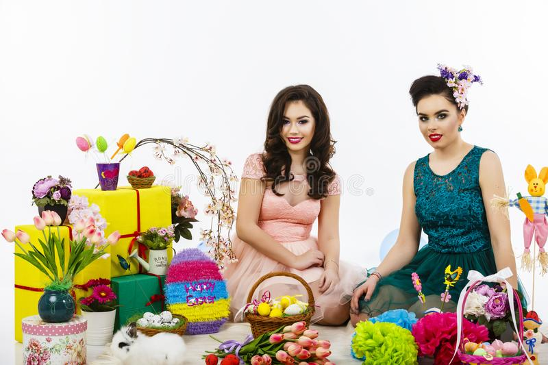 Two beautiful girlfriend girls, basket with eggs and flower decor. style makeup and hairstyle enjoy the Easter celebration stock images
