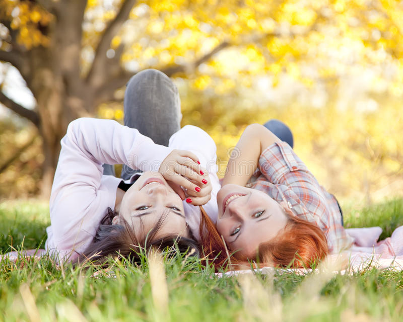 Two beautiful girlfriends at the autumn park stock photography