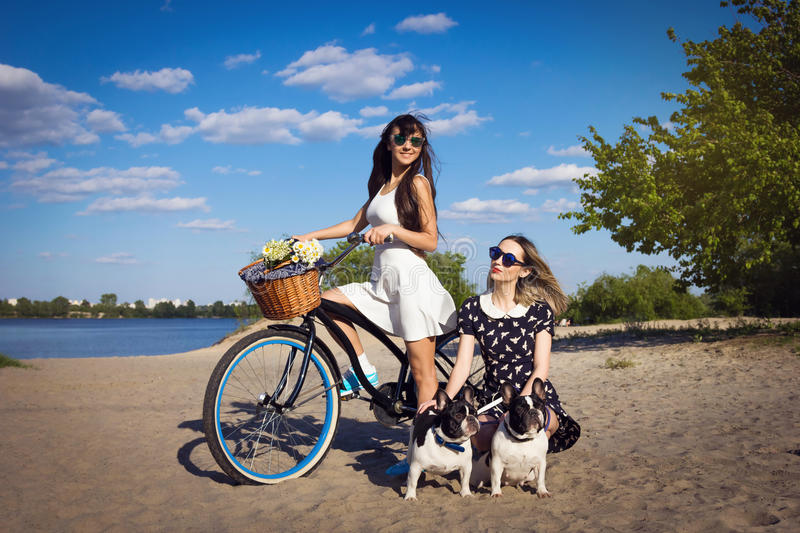 Two beautiful girls with bicycle and french bulldogs royalty free stock images