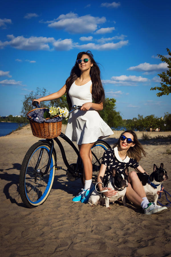 Two beautiful girls with bicycle and french bulldogs royalty free stock photos