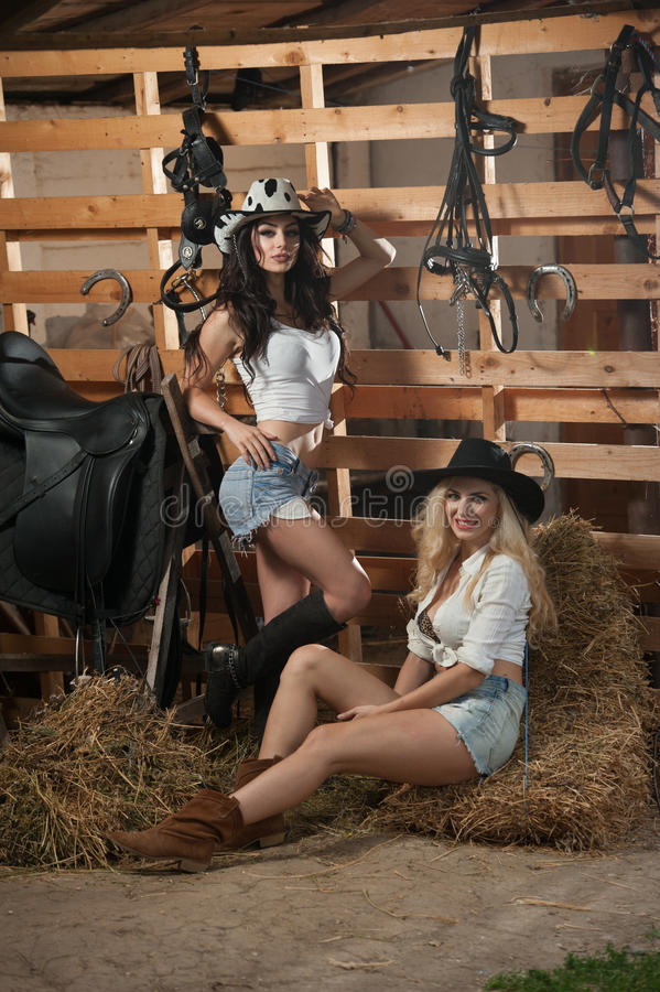 Two beautiful girls, blonde and brunette, with country look, indoors shot in stable, rustic style. Attractive women with hats stock photos