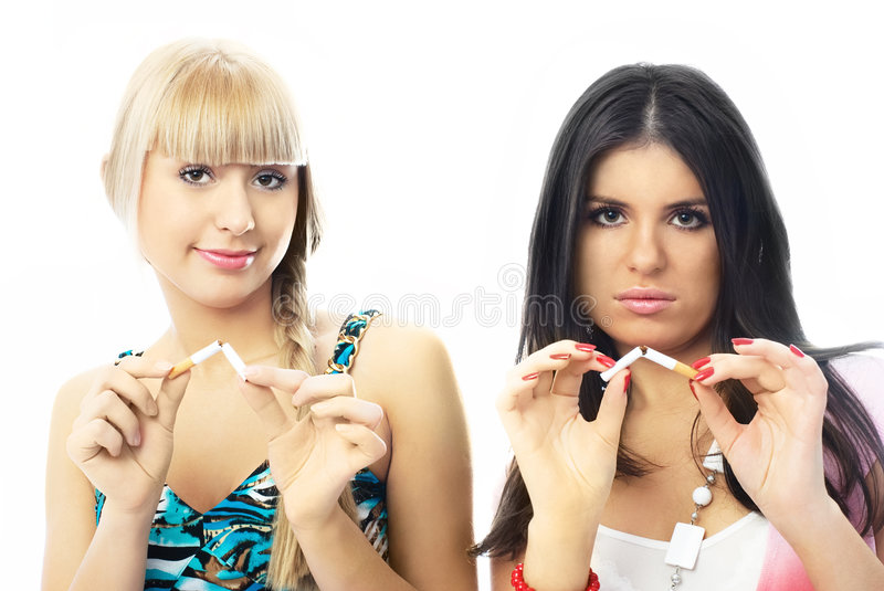 Two beautiful girls break up smoking. Two young beautiful women breaking cigarettes and looking at us seriously stock image
