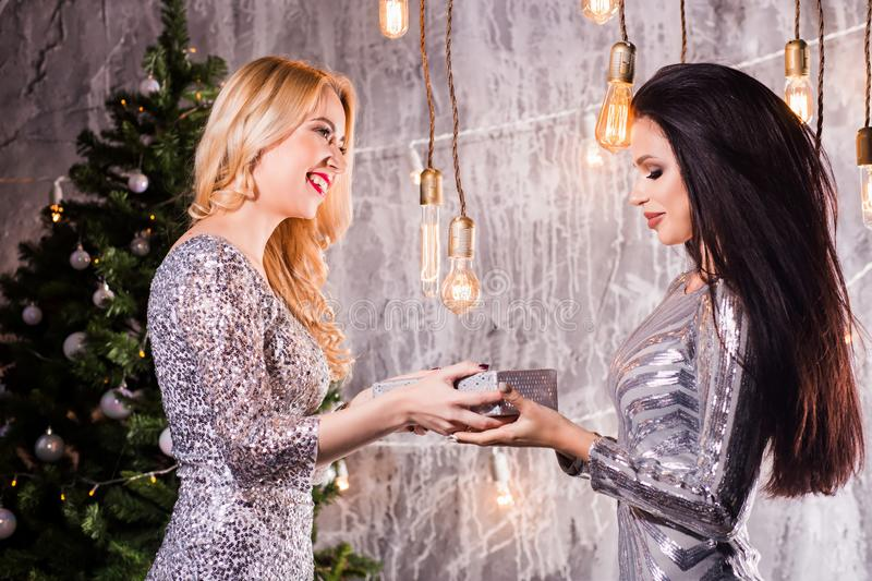 Two beautiful girls, brunette and blonde women giving each other Christmas gifts. New year, Christmas tree. New Year, holiday, celebration, winter concepts stock photo