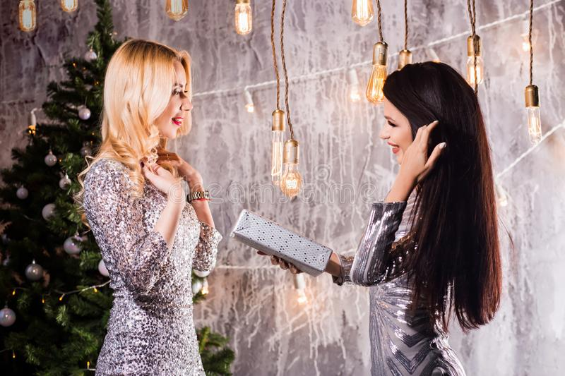 Two beautiful girls, brunette and blonde women giving each other Christmas gifts. New Year, holiday, celebration, winter concepts royalty free stock image