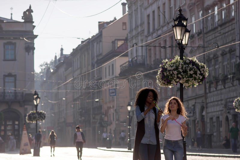 Two beautiful girls with bubble blowers walking in the downtown. One girl is black with nice curly hair. stock images