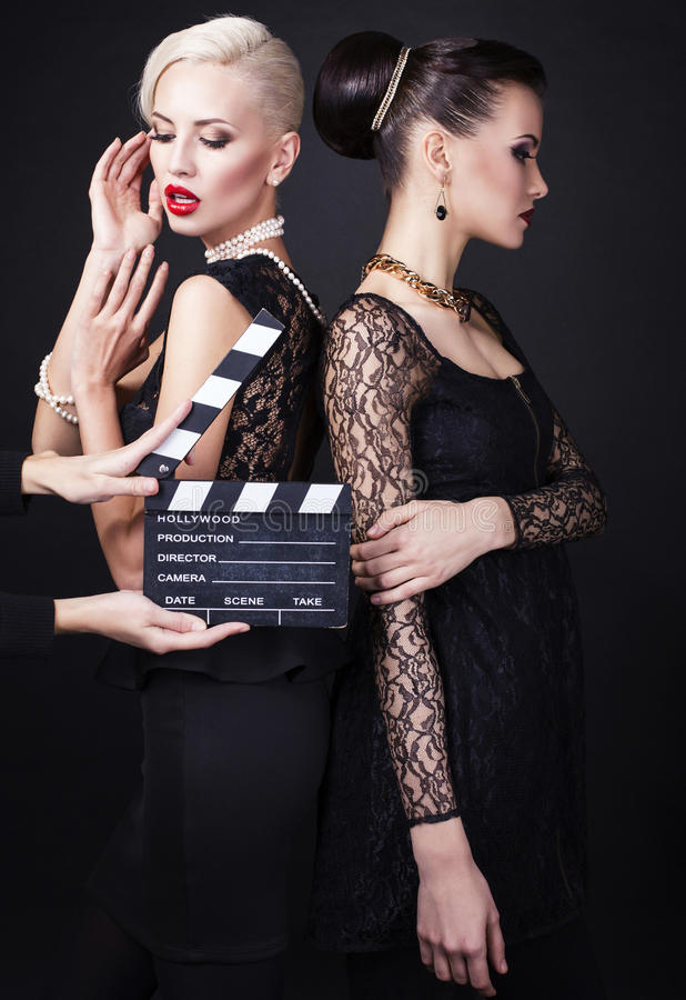 Two beautiful girls with cinema clapperboard stock images