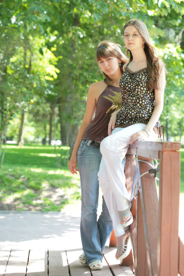 Two beautiful girls in city-park stock photo