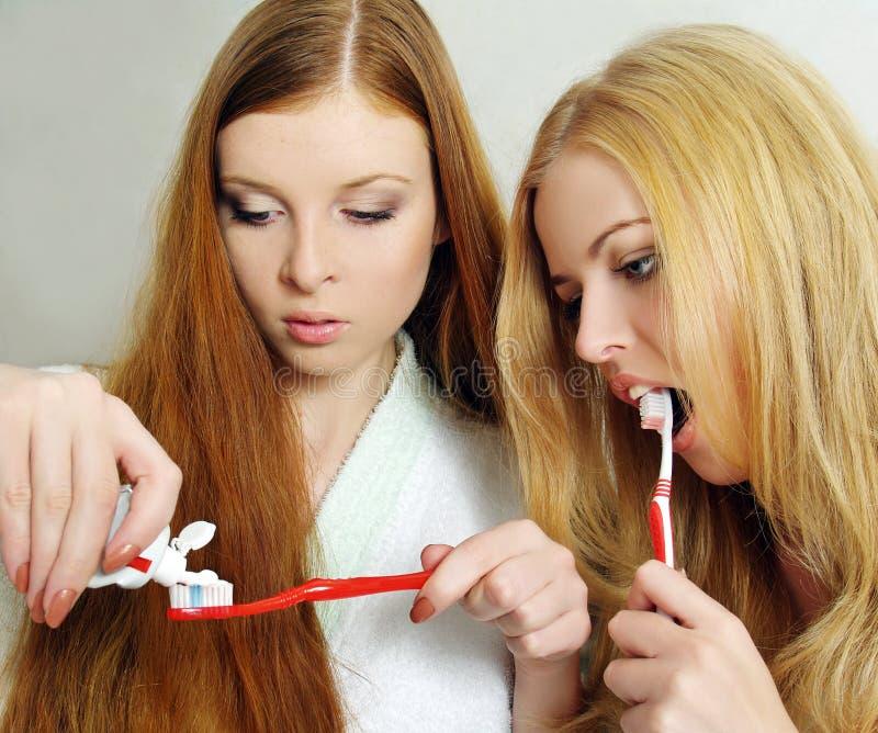 Two beautiful girls clean a teeth stock image