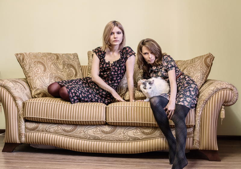 Two Beautiful Girls In Dresses Sitting On A Sofa Stock