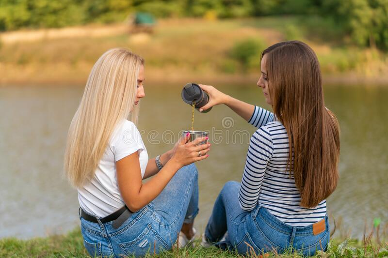 Two beautiful girls enjoy nature and drink hot tea on lakeshore with beautiful view.  royalty free stock photos
