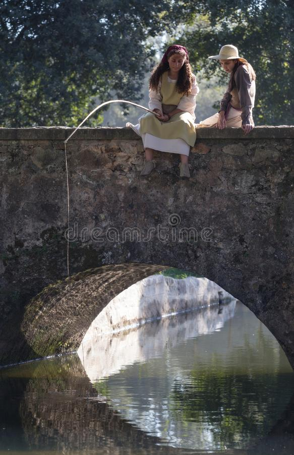 Two beautiful girls fishing from a bridge in a medieval event `Viagem Medieval em Terra de Santa Maria`, Santa Maria da Feira. Two beautiful girls fishing from royalty free stock images
