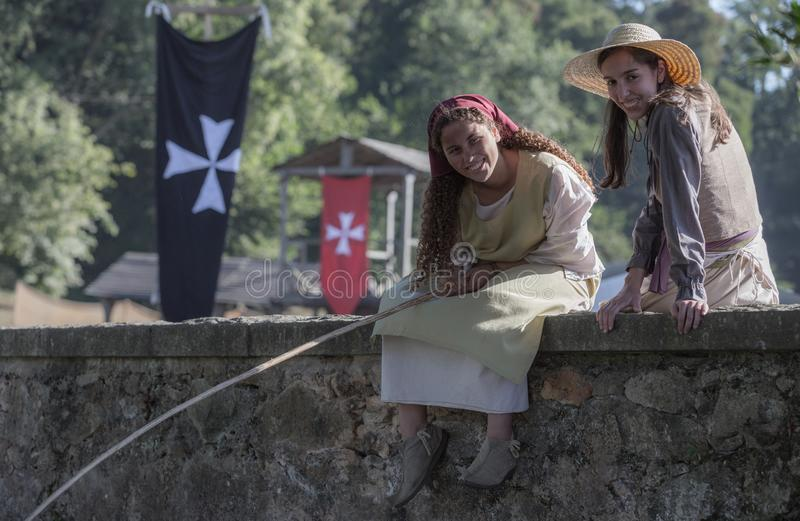Two beautiful girls fishing from a bridge in a medieval event `Viagem Medieval em Terra de Santa Maria`, Santa Maria da Feira. Two beautiful girls fishing from royalty free stock photo