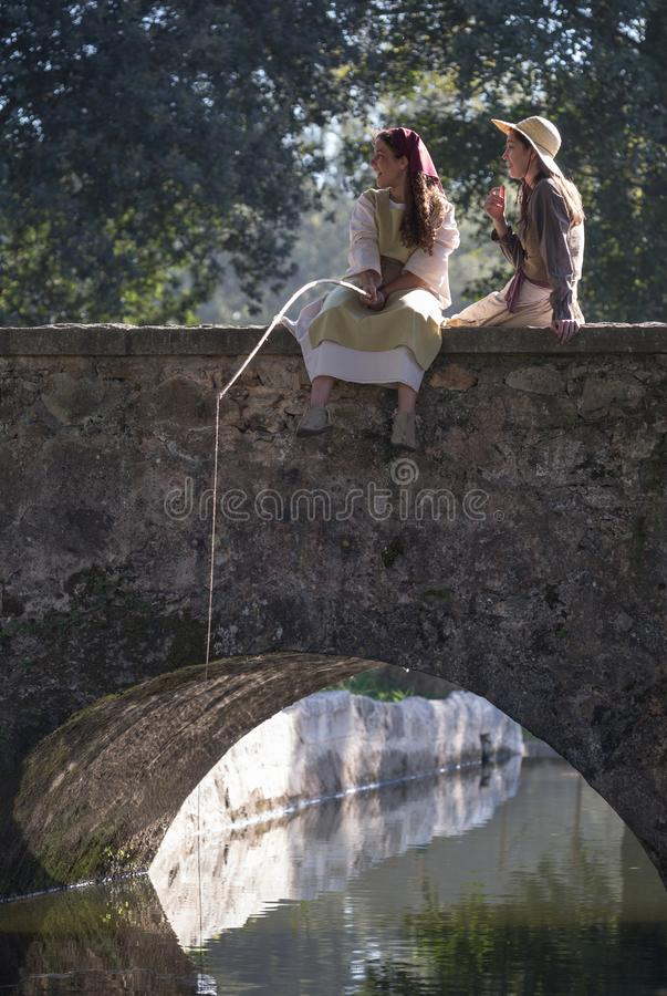 Two beautiful girls fishing from a bridge in a medieval event `Viagem Medieval em Terra de Santa Maria`, Santa Maria da Feira. Two beautiful girls fishing from royalty free stock image