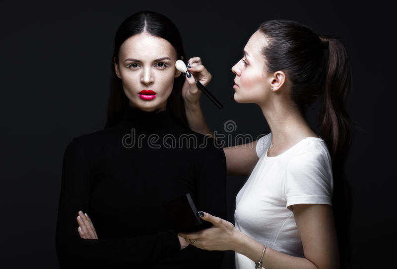 Two beautiful girls on photo shoot to apply face makeup . Beauty fashion model. Two beautiful girls on a photo shoot to apply makeup to the face. Beauty fashion royalty free stock photos