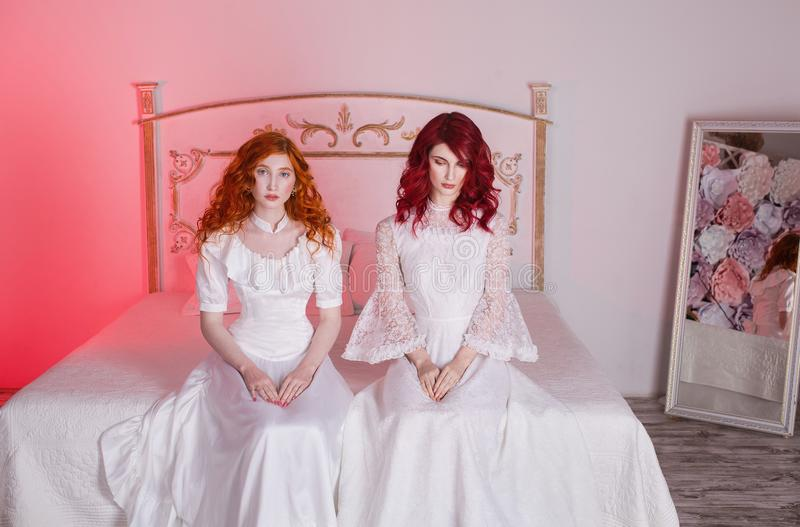 Two beautiful girls with red hair in a beautiful white wedding Victorian dresses stock photo