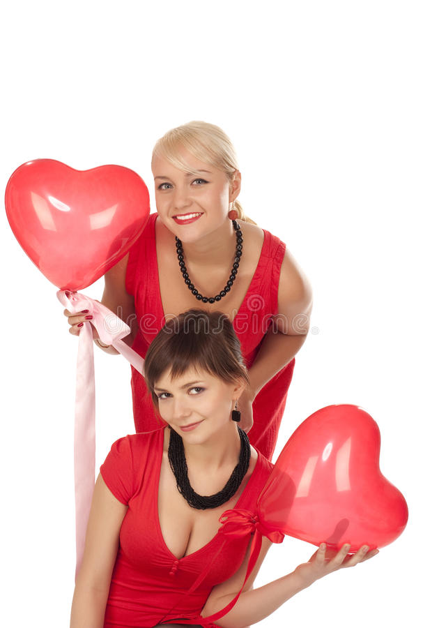 Two beautiful girls with red heart balloon stock photo
