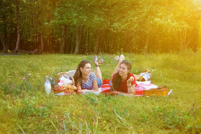 Two beautiful girls rest on a picnic in the forest stock photography