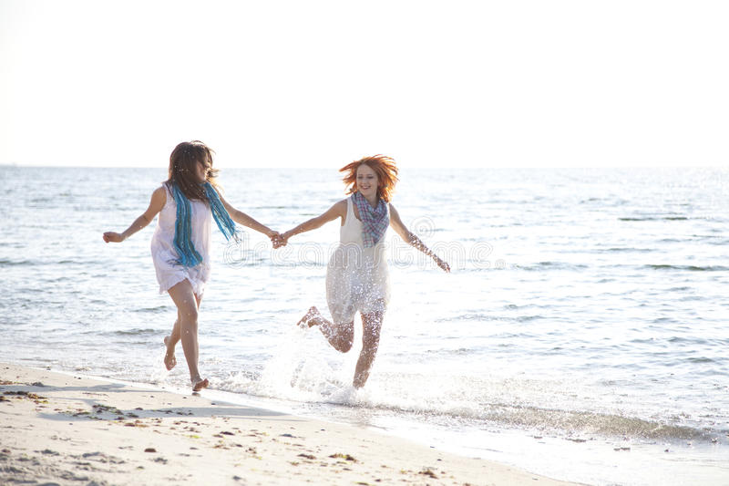 Two beautiful girls running on the beach. royalty free stock photography