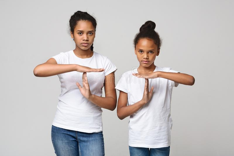 Two beautiful girls showing time out sign over grey background. Beautiful african teenaged girls showing time out sign over grey studio background royalty free stock images