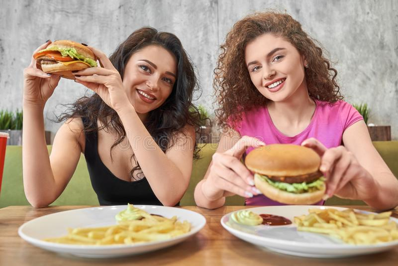 Two beautiful girls sitting in cafe, holding hamburgers. royalty free stock photo