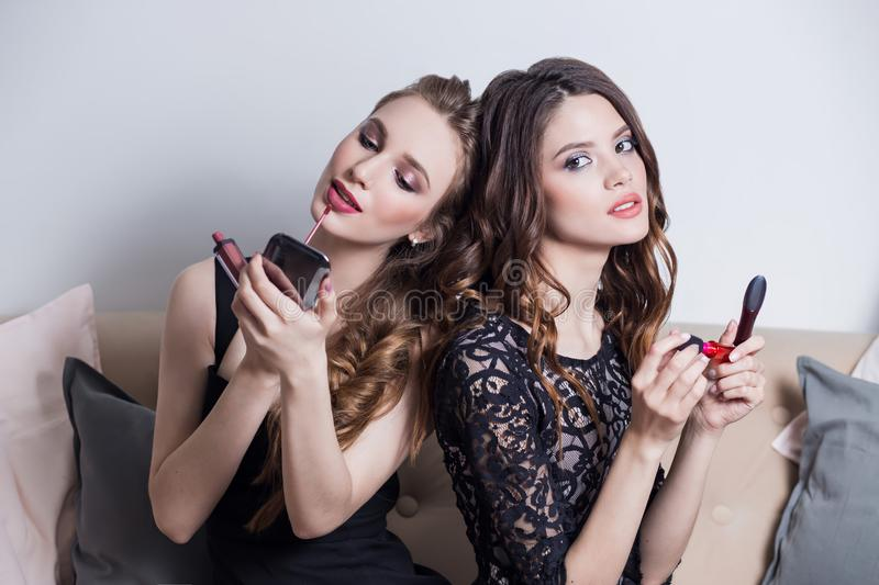 Two beautiful girls sitting on the sofa, makeup, looks at the mirror, causing a pink red lipstick, lip gloss, makeup, cosmetics, royalty free stock photography