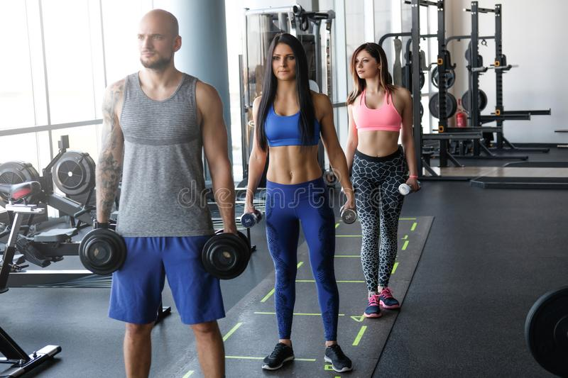 Two beautiful girls with their coach doing functional crossfit training with dumbbells in the gym. stock photo