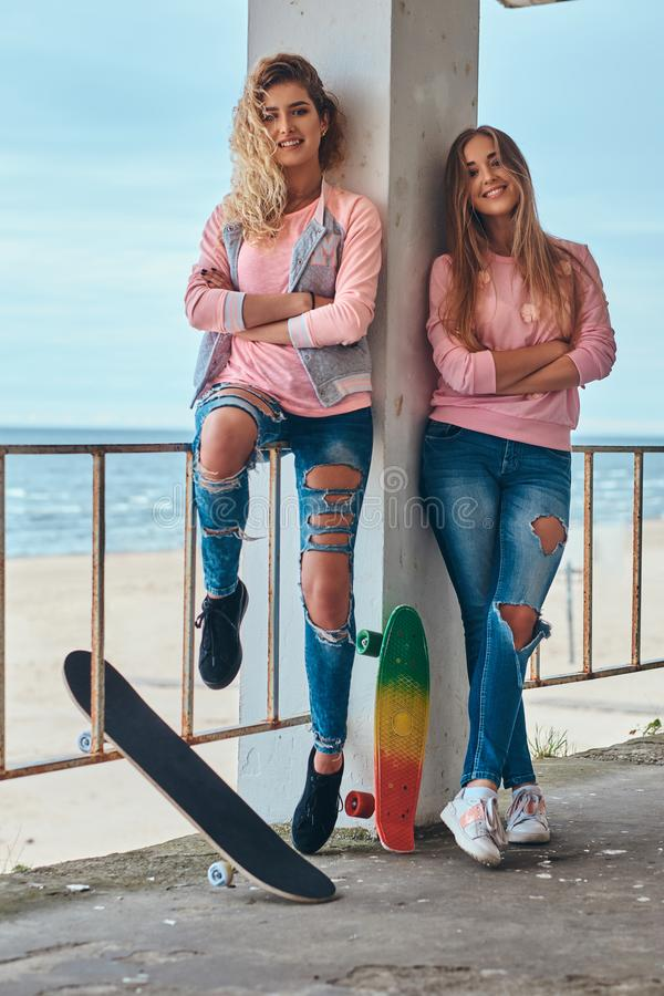 Two beautiful girls in trendy clothes posing with skateboards near a guardrail against a sea coast. royalty free stock image
