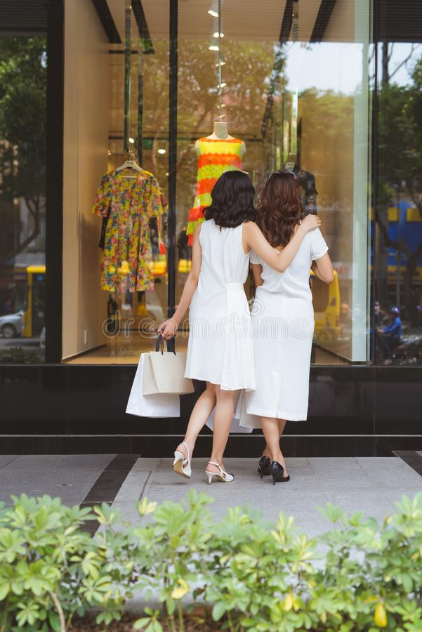 Two beautiful girls window shopping in the city.  royalty free stock image