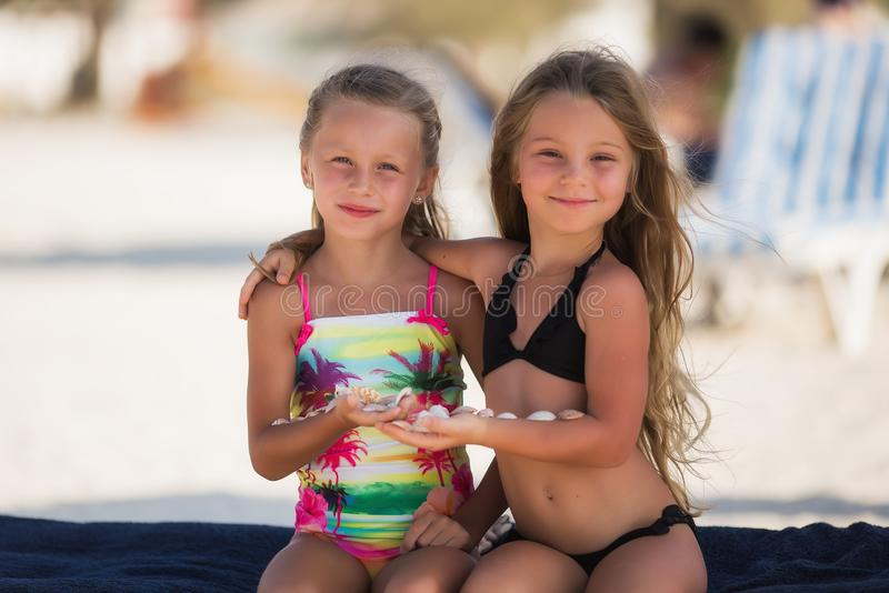 Two beautiful happy girl with shells in their hands stock photos