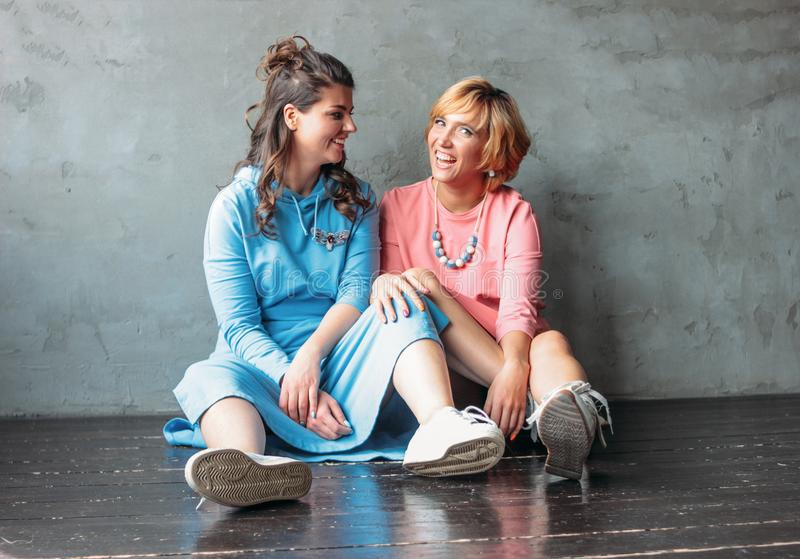 Two beautiful happy young women real friends in casual dress sit near concrete wall. Two beautiful happy young women real friends in the casual dress sit near royalty free stock photography