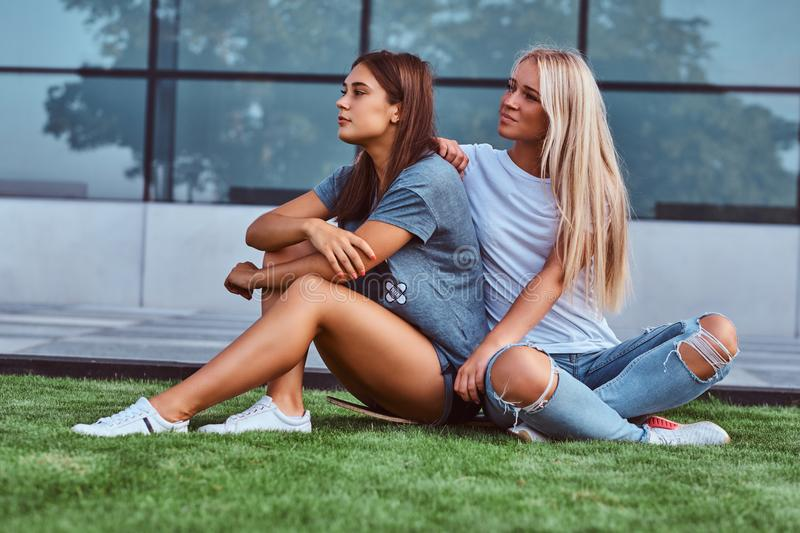 Two beautiful hipster girls sitting on grass with a skateboard on a background of the skyscraper. stock images