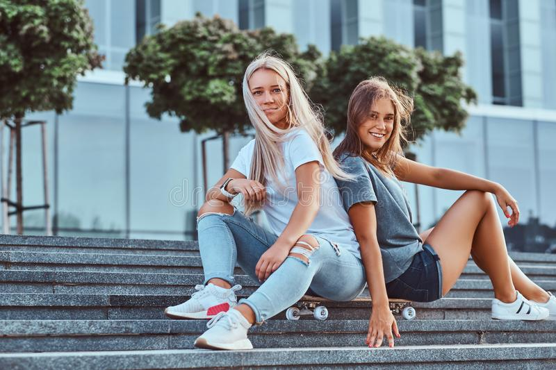 Two beautiful hipster girls sitting on steps with skateboard on a background of the skyscraper. royalty free stock photo