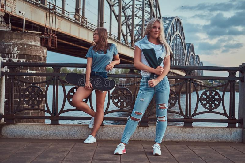 Two beautiful hipster girls standing with skateboard against a bridge. stock photography