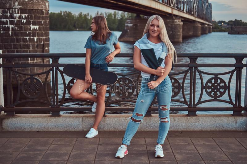 Two beautiful hipster girls standing with skateboard against a bridge. stock image