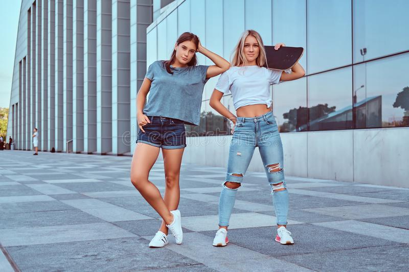 Two beautiful hipster girls standing with a skateboard on a background of the skyscraper. stock image