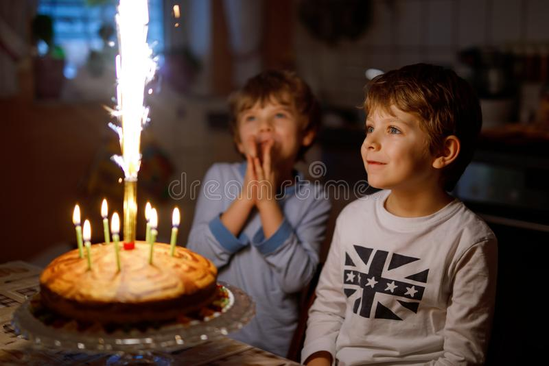Two beautiful kids, little preschool boys celebrating birthday and blowing candles royalty free stock photography