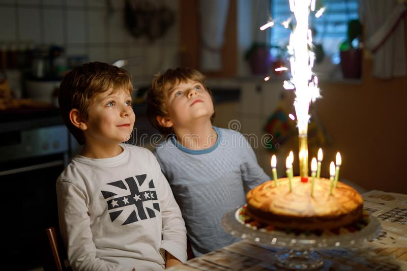 Two beautiful kids, little preschool boys celebrating birthday and blowing candles on homemade baked cake, indoor stock photos