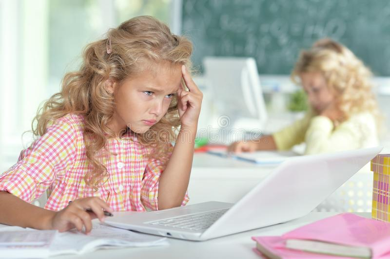 Two beautiful little girls working with computers royalty free stock photography