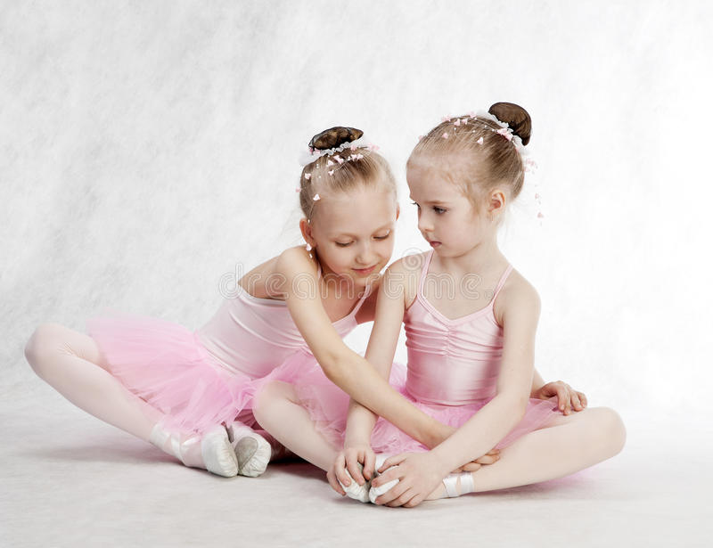 Two beautiful little princesses reading a magic book stock images