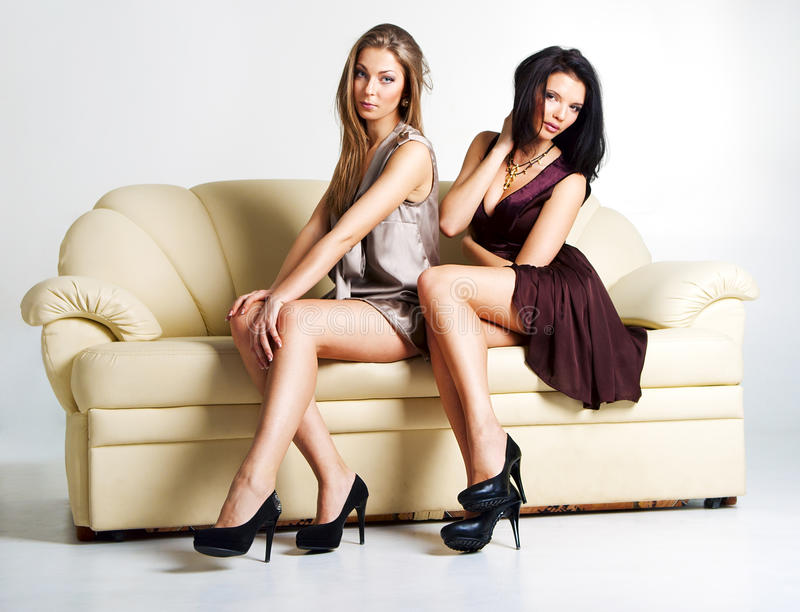 Two beautiful luxurious women sitting on a couch stock photo