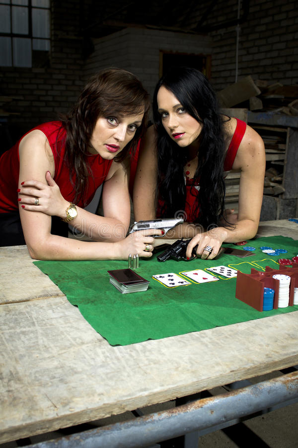 Two beautiful mafia ladies with guns. Two pretty ladies in role play. Both are standing beside a poker table with cards and chips royalty free stock image