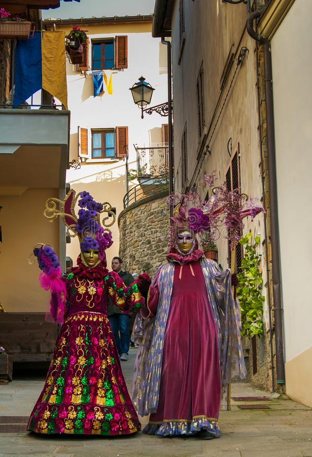 Two beautiful masquerade woman walking in the alley of Castiglion Fibocchi for carnival royalty free stock photos