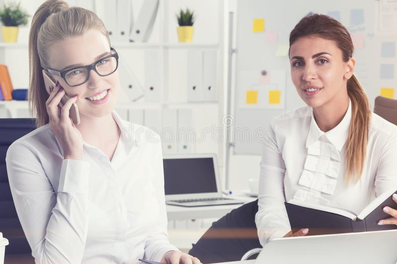 Two beautiful office employees working. Blonde busiensswoman in glasses is talking on her phone. He colleague with dark hair is holding a planner. Toned image royalty free stock photography